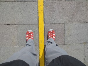 Feet straddling a yellow line supposed to mark the equator