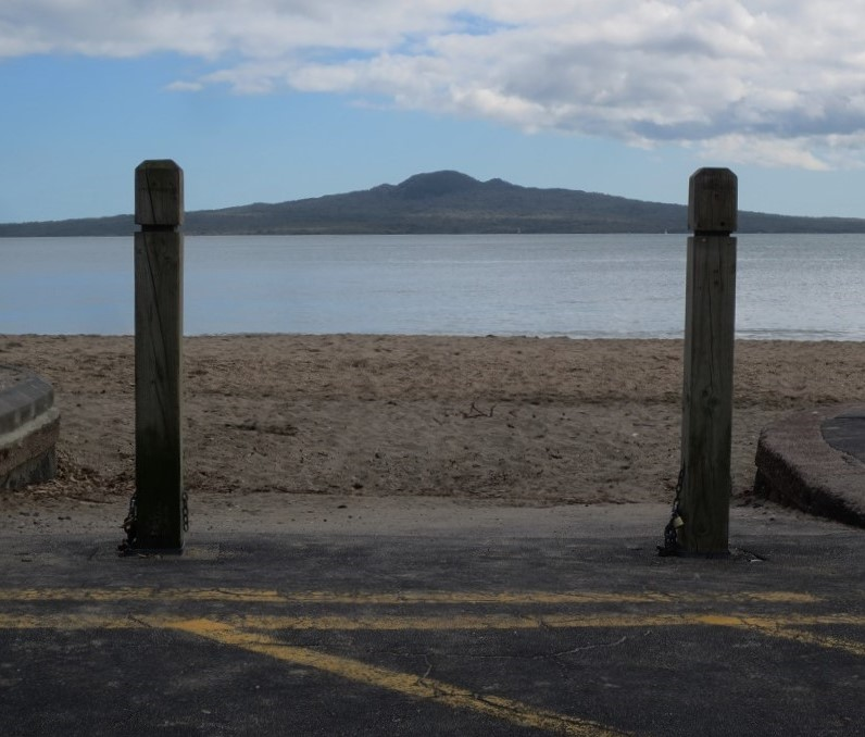 Volcanic cone island on horizon, framed by two wooden bollards. Beach in foreground.