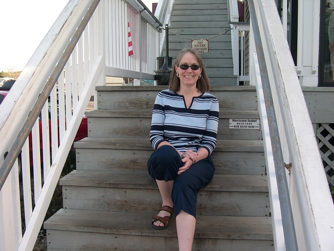 Isabel Gibson on wooden stairs beside high-water-mark plaque for Hurricane Isabel.