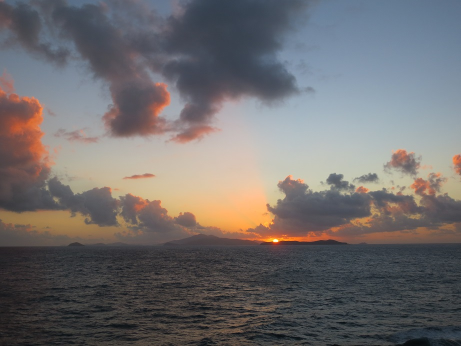 Sunrise over St. Thomas, with islands in silhouette beneath a pale blue sky.