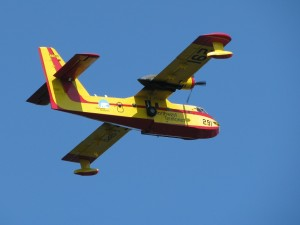 Airborne NWT water bomber in yellow and red colours against bright blue sky