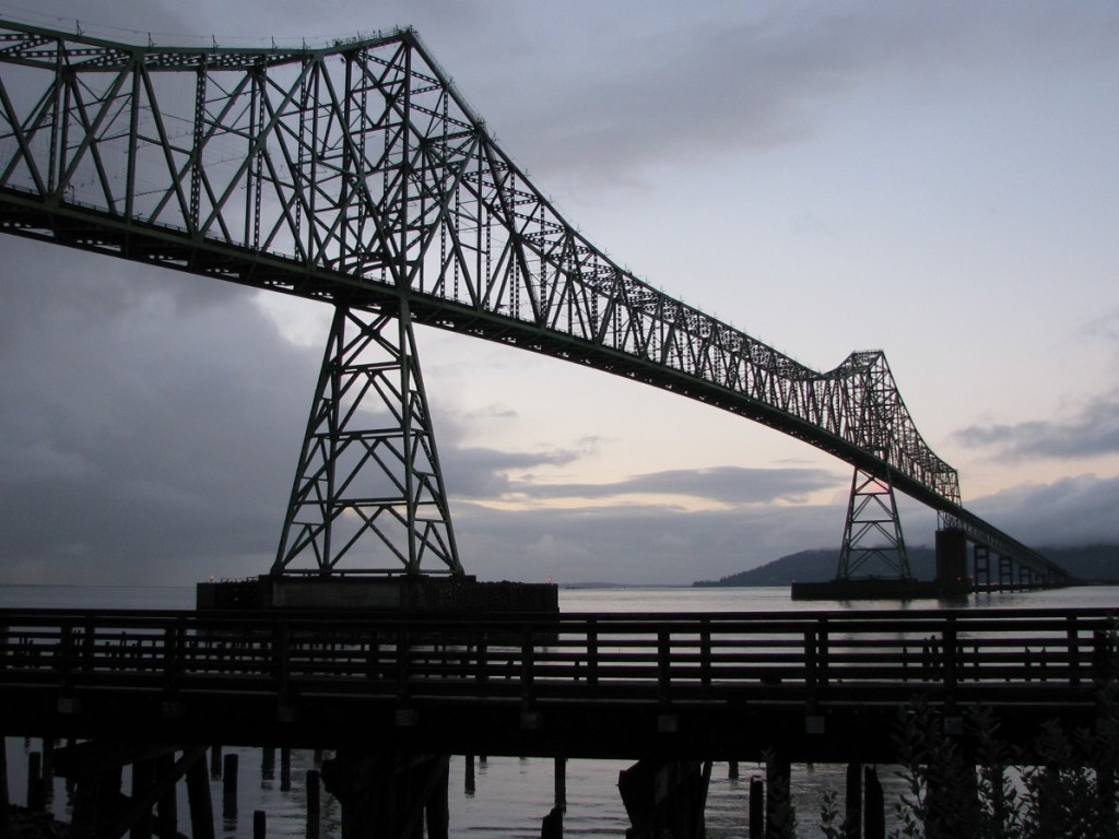 Late afternoon silhouette of metal bridge across Columbia River; wooden walkway in foreground.