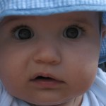 Close-up of baby with uncomprehending look on face.