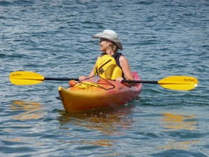 Red and yellow kayak; woman sitting therein, on bright, sunny day.