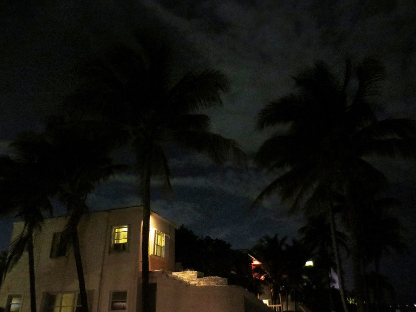 Night scene of stucco, two-storied hotel with palm trees.