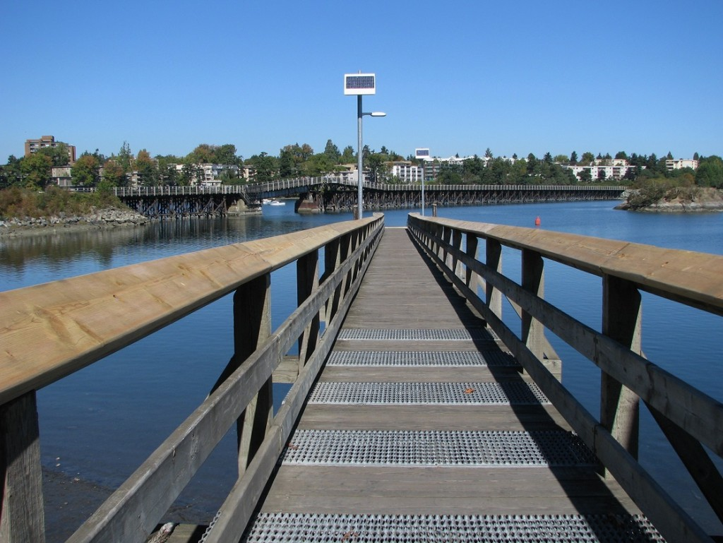 Wooden pier extends out into harbour; background shows wooden bridge over inlet.