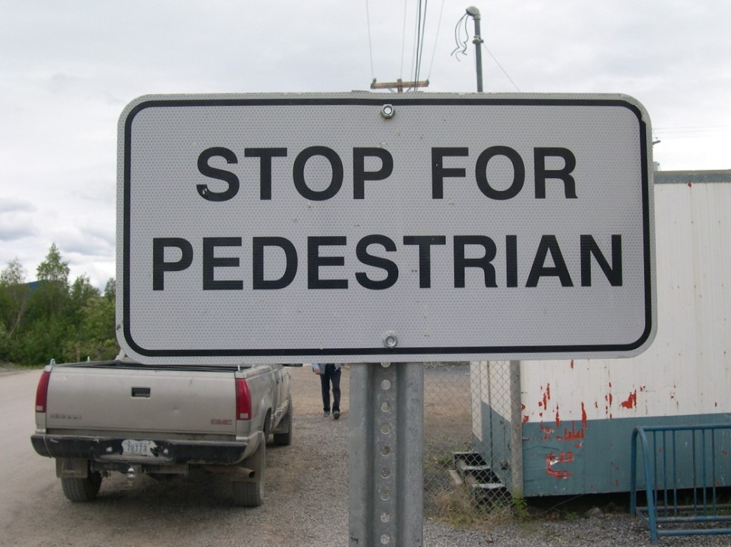 Black and white traffic sign: Stop for Pedestrian (singular)
