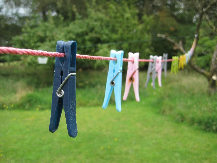 Multi-coloured plastic clothespins stretching along a red clothesline.