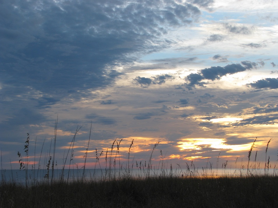 Grassy sand dune in foreground, Gulf of Mexico in background; sunset filling most of the photo.