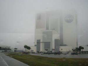 NASA administration building out a rain-streaked bus window.