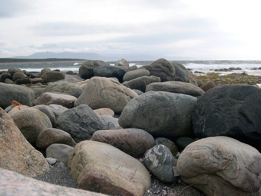 Ground-level view of beach rocks in foreground; ocean in background.