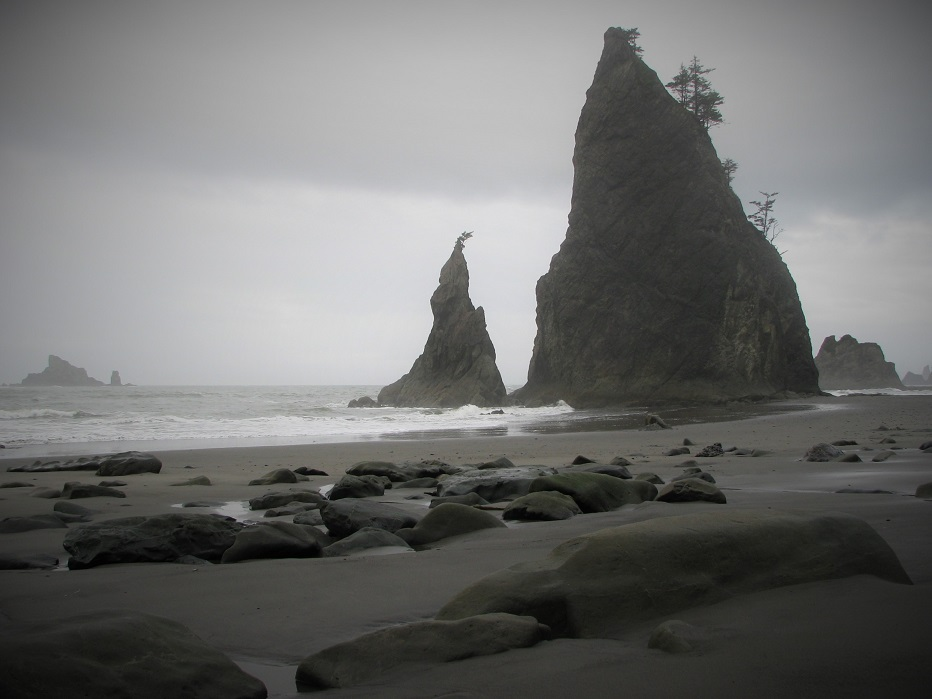 Black and white view of rainy-day beach with rock pinnacles