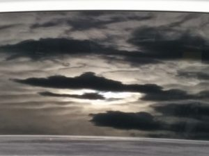Almost black and white rendering of cloudy sky reflected in minivan window.