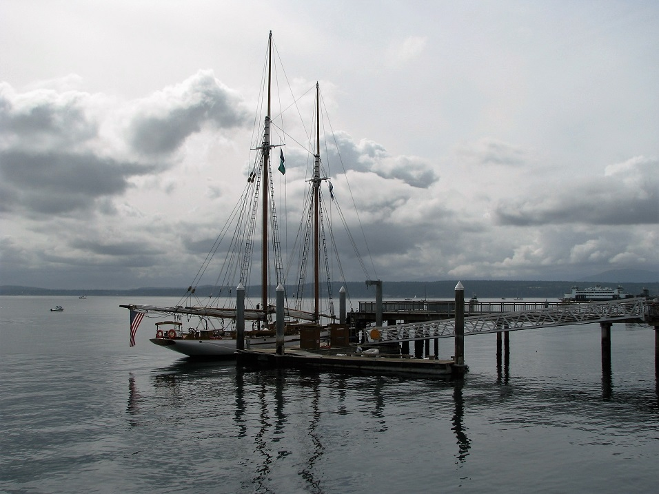 Sailboat berthed alongside dock; grey sky in background.