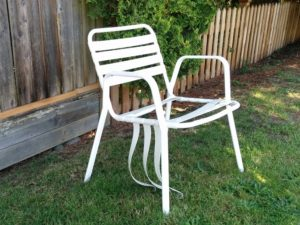 White lawn chair with broken plastic webbing, beside the sidewalk.
