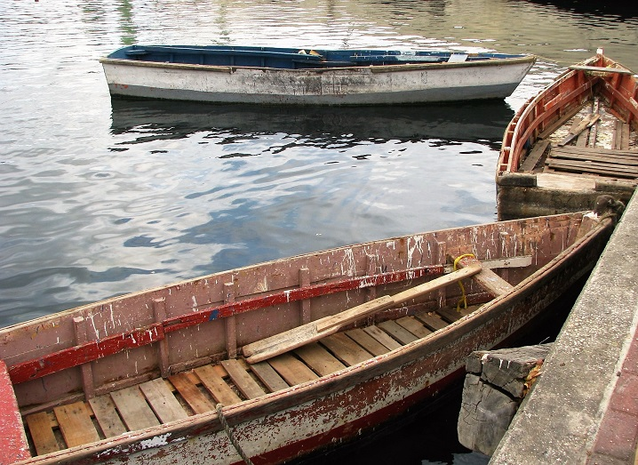 Three weathered seagoing rwoboats in Curacao harbour.