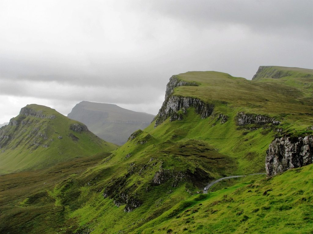 Rugged cliffs with thin skin of green in Scottish Highlands.