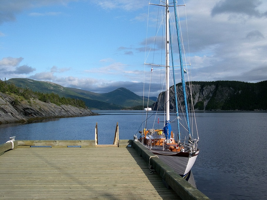 Sailboat alongside dock; mountains in background.