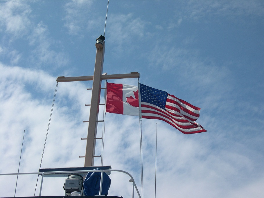 Canadian and American flags on ferry superstructure.
