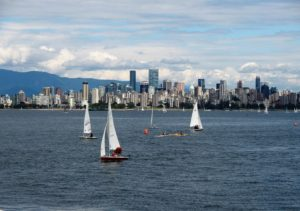 View of city across water; sailboats in foreground
