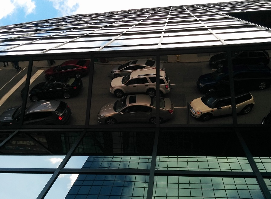 Reflection of cars in overhead, angled mirror tiles