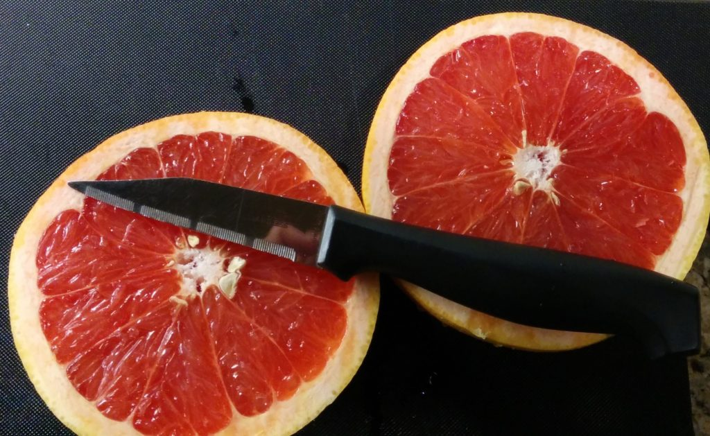Two halves of a red grapefruit.