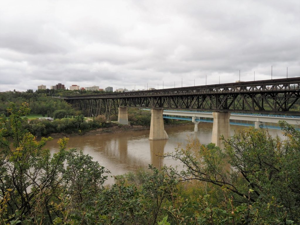 Trestle rail bridge across muddy North Saskatchewan River.