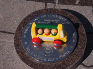 Toy bus at monument for geographic center of the USA