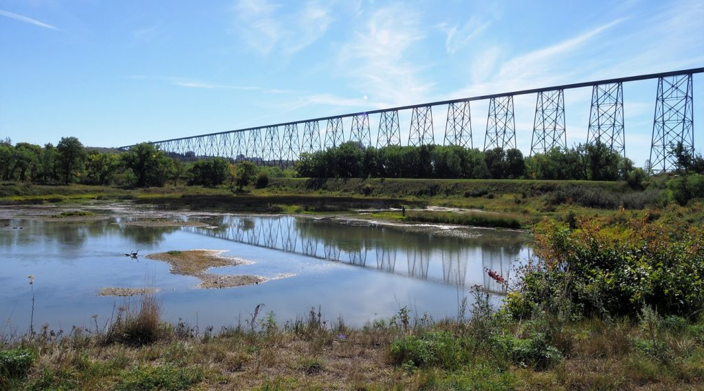 Angled view of High Level Bridge and its reflection in Oldman River in foreground.