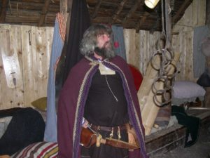Actor in period dress in reconstructed Norse settlement.