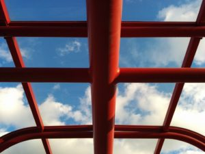 Red metal beams of bus shelter roof; showing blue sky through the plexiglass.