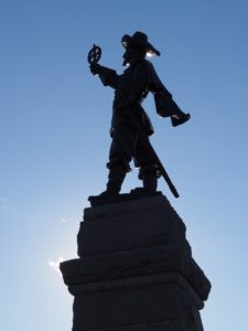 Silhouetted statue of Samuel de Champlain, against a blue sky.