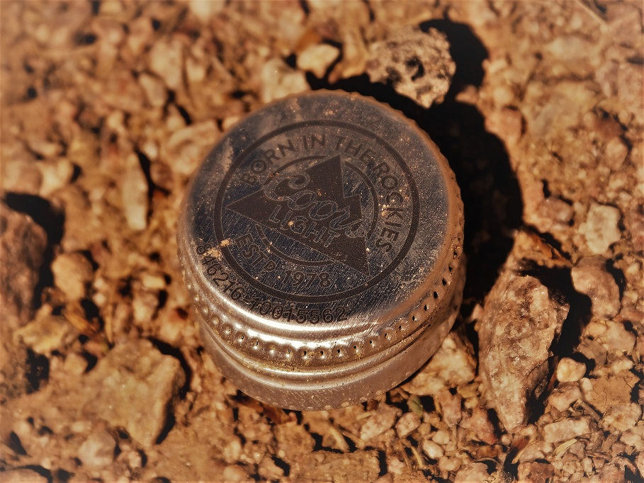 Coors Light bottlecap on gravel bed.