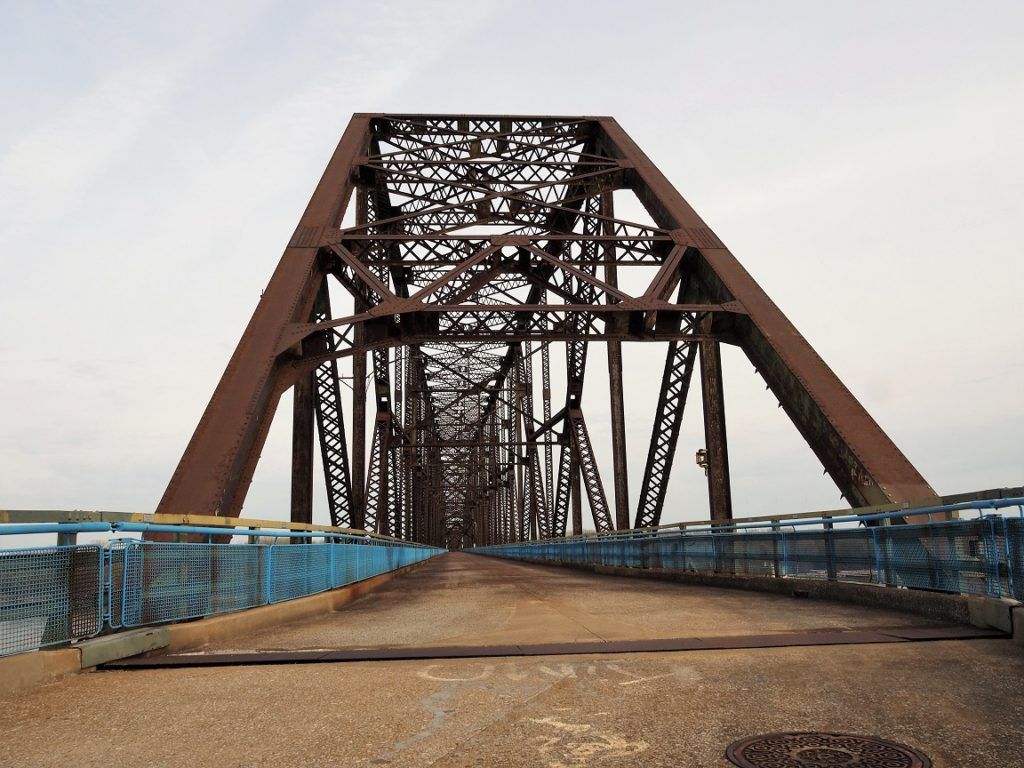 Deck level view of truss structure of bridge.