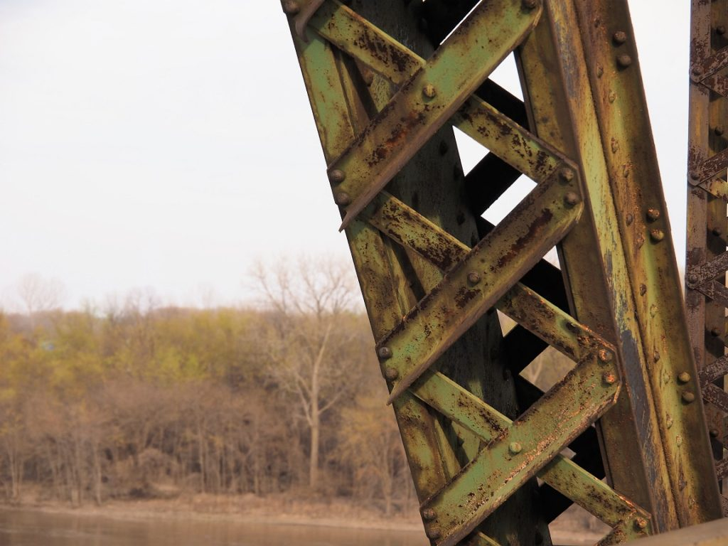 Close-up of green and rusty truss structure with new foliage in background.