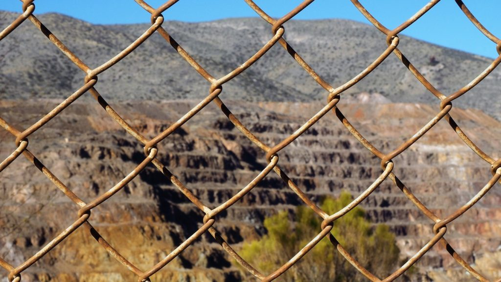 Rusty fence in foregroun; copper pit in background.