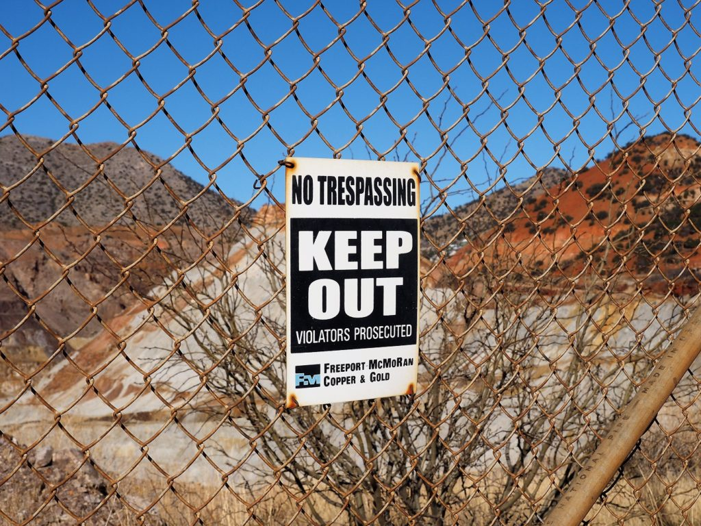 Chain-link fence with no trespassing sign