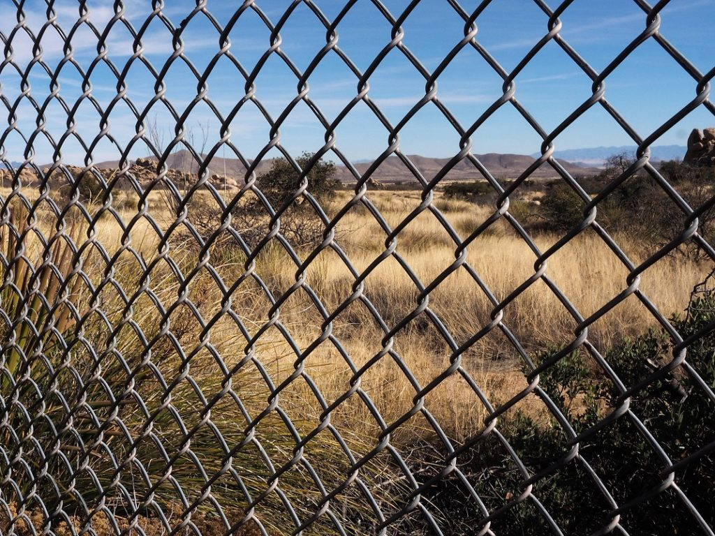 Chain-link fence in foreground; desert in background.