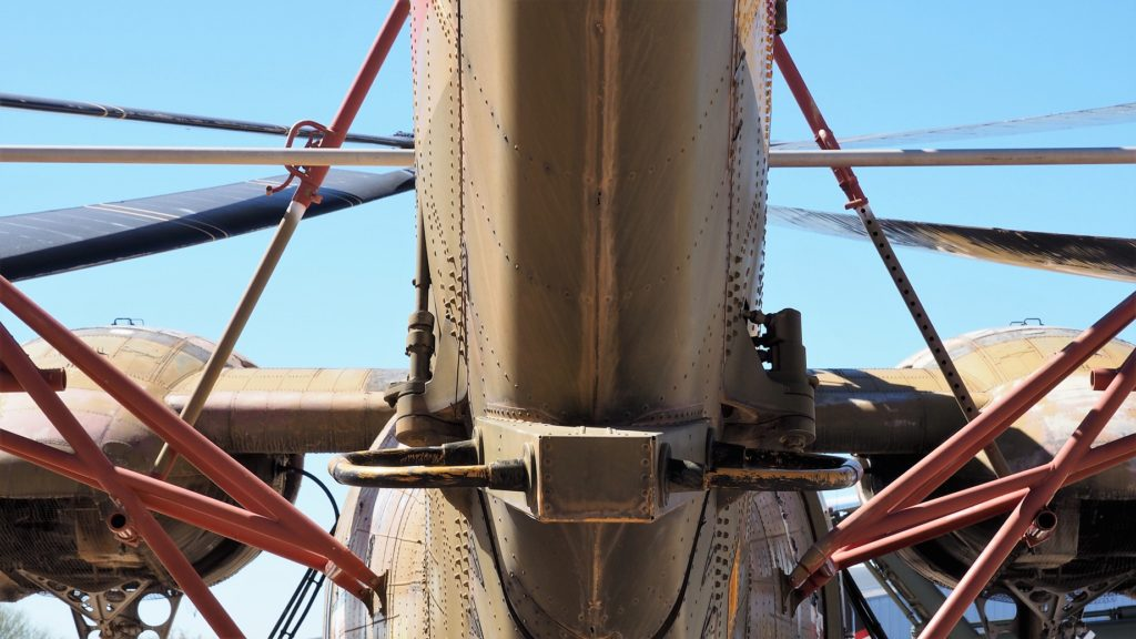 View of complex strut structure of helicopter from underneatn the tail.