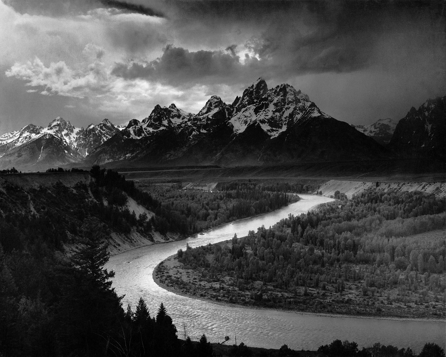 B&W photo of snow-capped mountains at sunset with oxbow of river in foreground