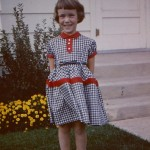 Five-year-old girl in 1957; gingham dress and saddle oxfords.