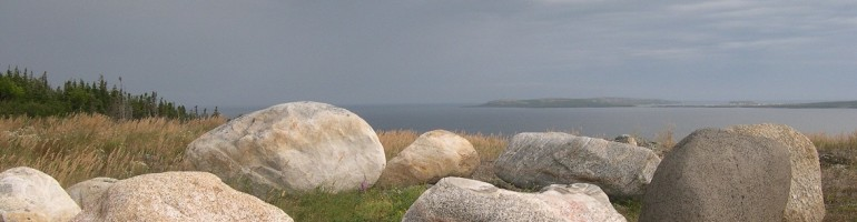 Close-up of rocks on a hillside overlooking sea in the background.