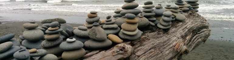 Smooth stones piled up on driftwood log on beach.