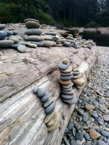 Smmoth stones piled on driftwood log on beach
