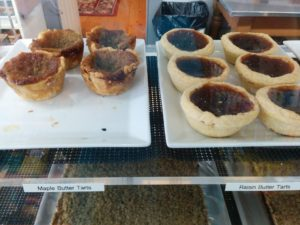 Bakery shelf with maple and raisin butter tarts.