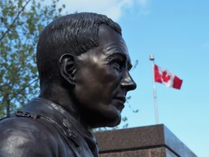 Bust of John McCrae with Canadian flag in background.