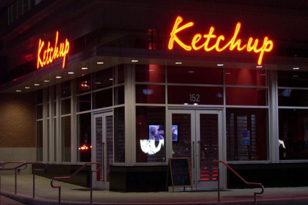 Corner view of Ketchup restaurant at night.
