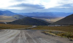 Gravel roadbed of Dempster Highway snaking around hills an d disappearing into the mountain range on the horizon.