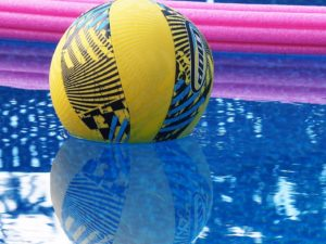 Blue and yellow ball floating in pool, flanked by pink noodle.