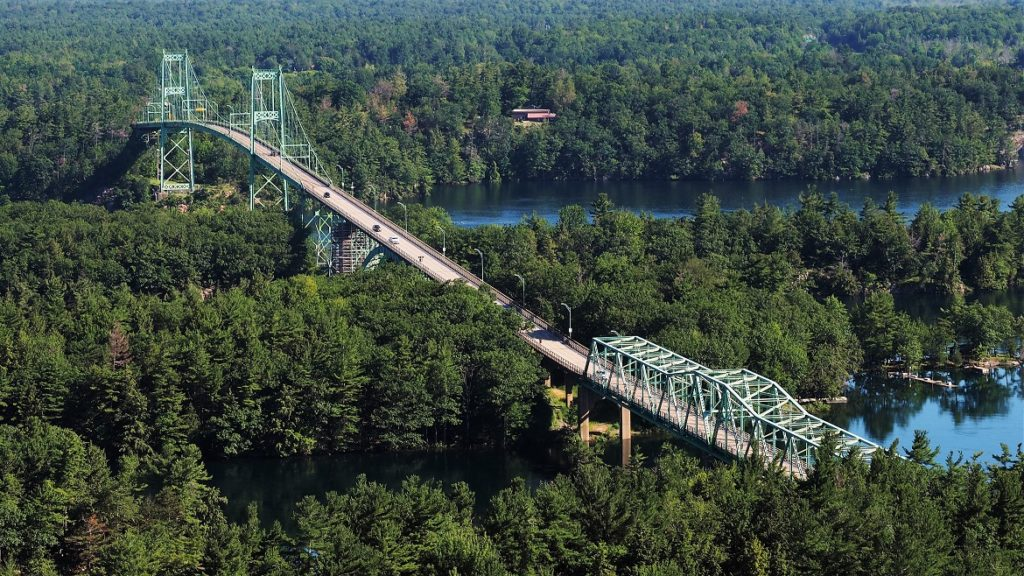 Minty-green bridge (drive-through truss and cable-stayed) snaking through dark-green trees.